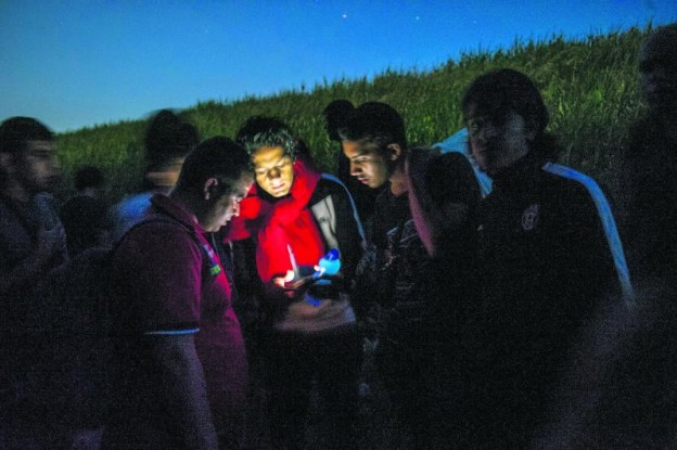 MARTONOS, SERBIA - June 2: Syrian refugees get directions on their phone while traveling through the woods near the Hungarian border on June 2, 2015 in Martono, Serbia. The group walked several miles along the Tisza river at sunset to pass through the border with Hungary at night to avoid the police. Refugees seeking asylum are passing through routes in Eastern Europe in greater numbers as countries like Hungary consider plans to fence off their borders. (Photo by Ann Hermes/The Christian Science Monitor via Getty Images) Refugees48