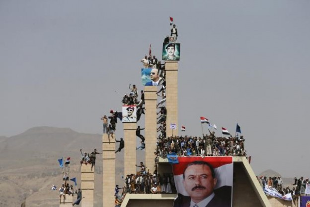 Supporters of Yemen's former President Ali Abdullah Saleh climb pillars of the Unknown Soldier Monument during a rally marking one year of Saudi-led air strikes in Yemen's capital Sanaa March 26, 2016. REUTERS/Khaled Abdullah