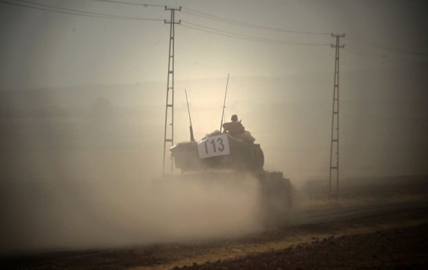 This picture taken on August 24, 2016 shows a Turkish army tank driving towards Syria  in the Turkish-Syrian border city of Karkamis, in the southern region of Gaziantep. Turkey's army backed by international coalition air strikes launched an operation involving fighter jets and elite ground troops to drive Islamic State jihadists out of a key Syrian border town. / AFP PHOTO / BULENT KILIC