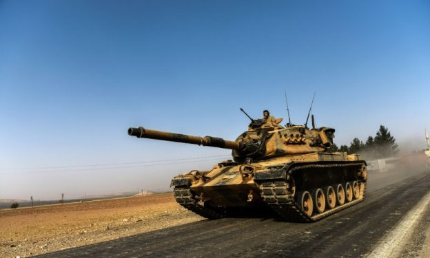 TOPSHOT - A Turkish army tank drives towards Syria in the Turkish border city of Karkamis, in the southern region of Gaziantep on August 24, 2016. Turkey's army backed by international coalition air strikes launched an operation involving fighter jets and elite ground troops to drive Islamic State jihadists out of a key Syrian border town. / AFP PHOTO / BULENT KILIC